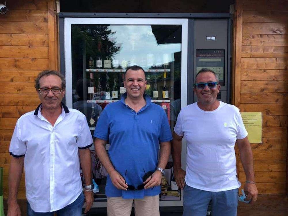 Al centro, il presidente di Terre d'Oltrepò, Andrea Giorgi, insieme ai fratelli Saviotti davanti al primo self service del vino in Oltrepò Pavese